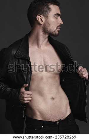 Beautiful muscular male model with nice abs in a jacket - stock photo