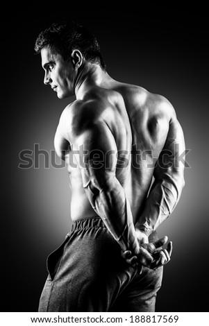 Beautiful muscular man bodybuilder posing back over dark background. - stock photo