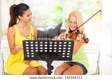 beautiful music teacher tutoring young girl to play violin - stock photo