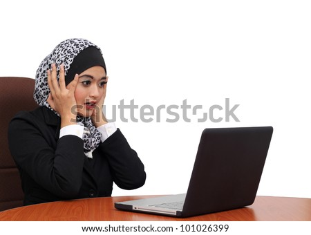 beautiful muslim business woman scared, terrified sitting at the desk working using laptop looking at screen, isolated over white background, computer problem concept - stock photo