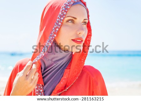 beautiful muslim caucasian (russian) woman wearing red dress rel - stock photo