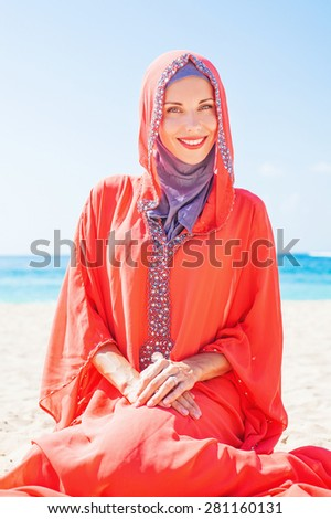 beautiful muslim caucasian (russian) woman wearing red dress relaxing on a beach - stock photo