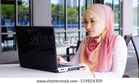 Beautiful Muslim girl with laptop at the cafe - stock photo