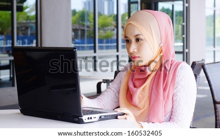Beautiful Muslim girl with laptop at the cafe