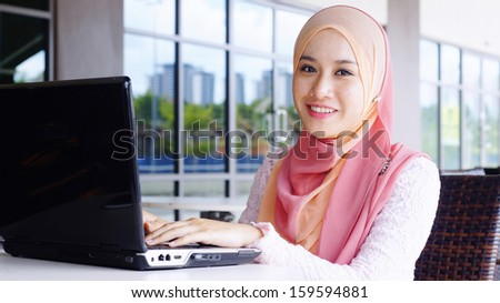 Beautiful Muslim girl with laptop at the cafe smiling - stock photo