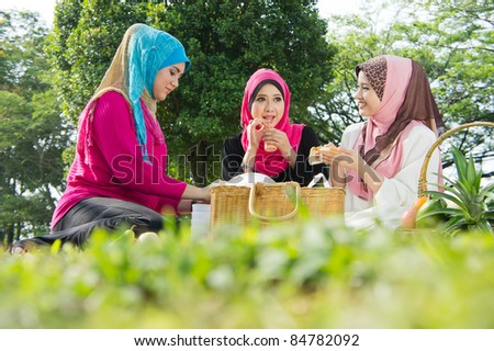 Beautiful Muslim girlfriends on picnic at park - stock photo