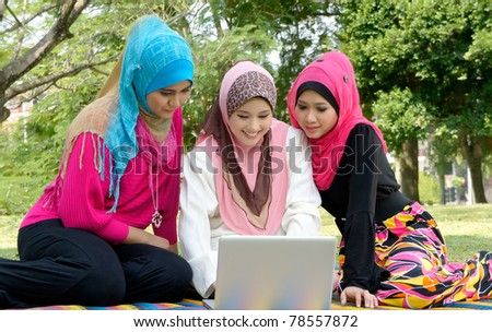 Beautiful Muslim girlfriends on picnic while surfing internet at park