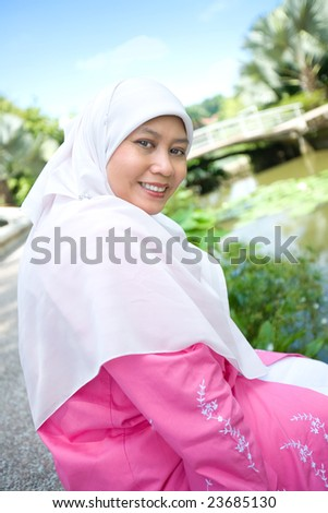 Beautiful Muslim Malay woman smiling in an outdoor park