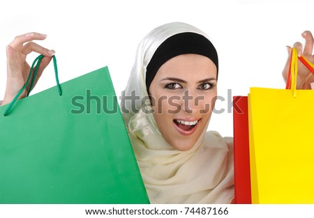 Beautiful Muslim traditional but modern woman holding shopping bags - stock photo