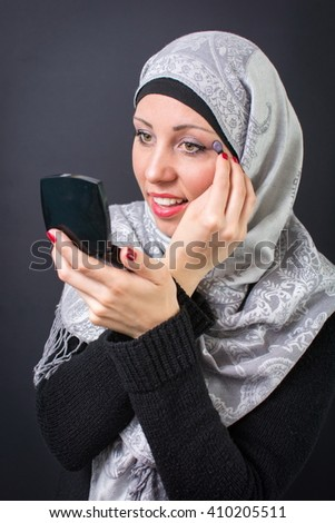 Beautiful muslim woman applying eyeshadow - stock photo