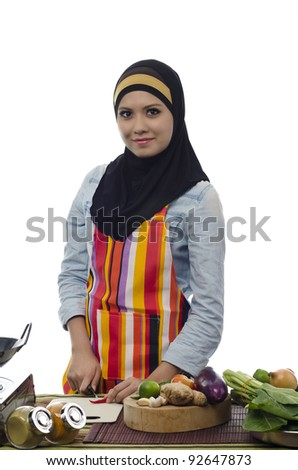 Beautiful muslim woman cooking healthy food in the kitchen