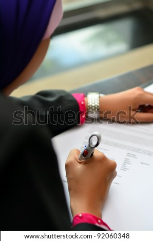 Beautiful Muslim woman fill in form - stock photo