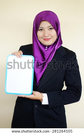 Beautiful Muslim woman holding a white board - stock photo