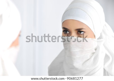 Beautiful Muslim woman looking at mirror - stock photo