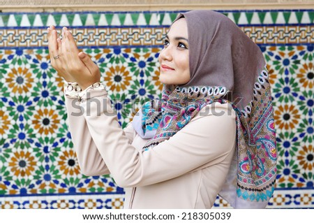 Beautiful muslim woman praying beside the islamic background - stock photo