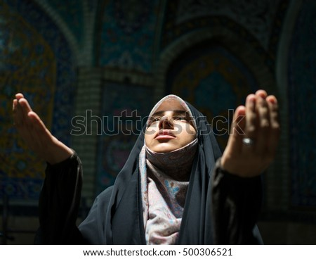 Beautiful Muslim woman praying inside dark mosque
