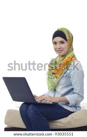 Beautiful muslim woman smiling with laptop on her laps - stock photo