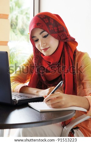 Beautiful muslim woman wearing red scarf writing beside a notebook at a cafe - stock photo