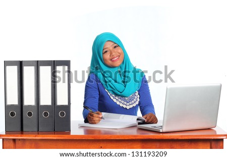 Beautiful muslim woman wearing scarf writing beside a notebook and file isolated on white