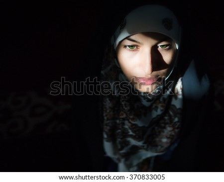 Beautiful Muslim young woman in darkness - stock photo