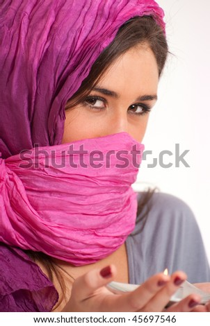 Beautiful mysterious exotic woman holding a candle - stock photo