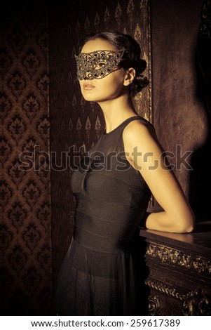 Beautiful mysterious stranger girl in venetian mask. Carnival, masquerade. Jewellery, gems. - stock photo