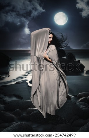 Beautiful Mysterious woman in long dress at ocean beach. Fantasy woman. Water Goddess. Book cover. - stock photo