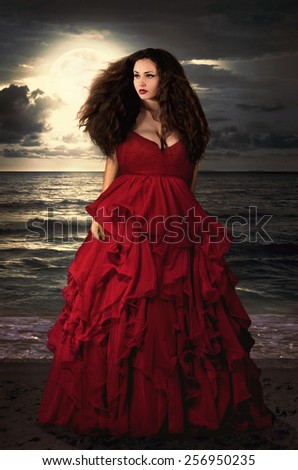Beautiful Mysterious woman in long red dress at ocean beach. Fantasy woman. Water Goddess. Book cover. - stock photo