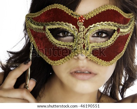 Beautiful mysterious woman's face behind ornate red and gold mask - stock photo
