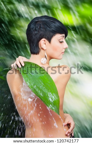 Beautiful naked back of young woman closing by palm leaf off splash of water against wet green background