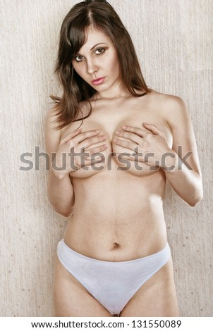 Beautiful naked brunette covers arms chest. - stock photo