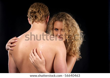 Beautiful naked couple with curly hair over black background