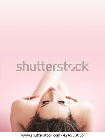 Beautiful naked female model over pink background
