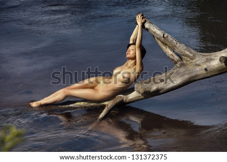 beautiful naked girl lying on a log in the lake as a mermaid - stock photo