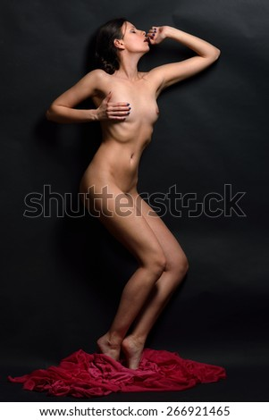 Beautiful naked sexy woman  posing in studio with dark background. Concept picture with red rope. - stock photo