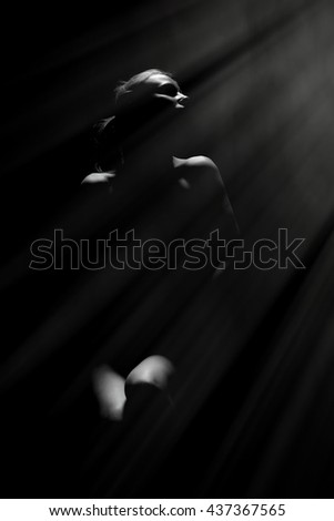 beautiful naked woman in dark with light rays, monochrome image