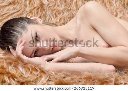 Beautiful naked woman laying on a fur. Torso portrait with naked breast. - stock photo