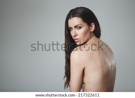 Beautiful naked woman looking at camera. Nude female model against grey background with copy space.