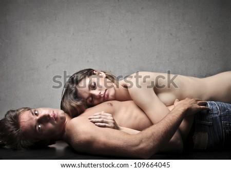 Beautiful naked woman lying on her boyfriend - stock photo