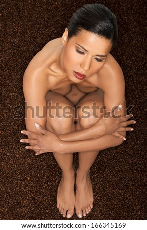 Beautiful naked woman on coffee beans background. - stock photo