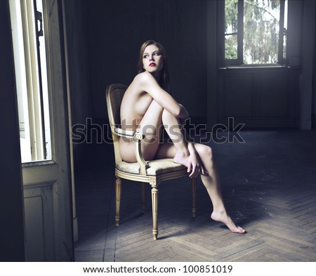 Beautiful naked woman sitting on an old chair in an empty room - stock photo