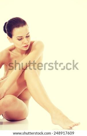 Beautiful naked woman sitting on the floor. - stock photo