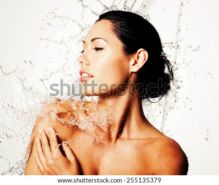 Beautiful naked woman with wet body and splashes of water - stock photo