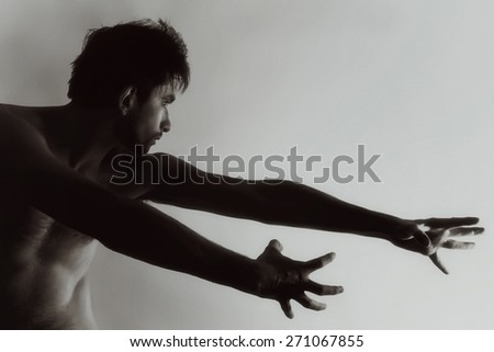 Beautiful naked young man with muscular bodyon a light background - stock photo