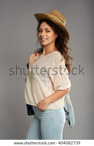 Beautiful native american cowgirl in straw hat and blue jeans - stock photo
