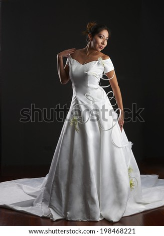 Beautiful Native American model wearing white bridal gown in studio.