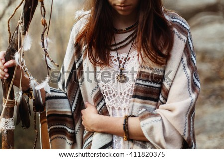 beautiful native indian american woman holding pikestaff with dreamcatcher on background of woods - stock photo