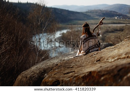 beautiful native indian american woman shaman  sitting on rocks and looking at woods and river - stock photo