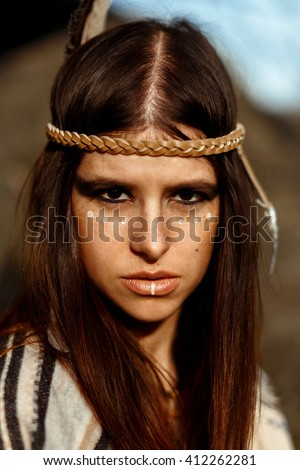 beautiful native Indian American woman with warrior shaman make up on background of woods - stock photo
