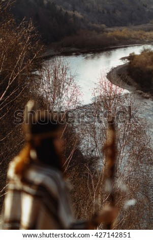 beautiful native indian american woman with warrior shaman make up sitting on rocks on background of woods and river - stock photo